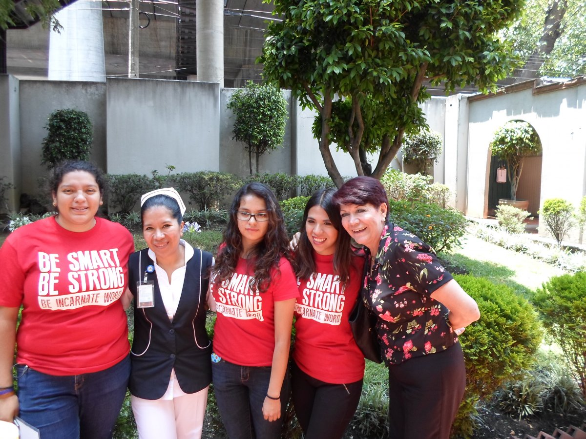 Three students, Graciela, and a nurse infront of a ministry
